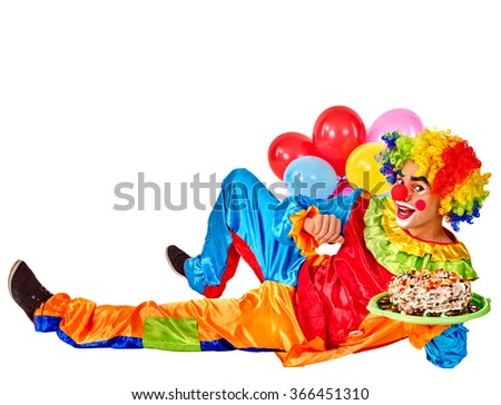 Happy birthday clown holding cakes and bunch of balloons lying on floor.  Isolated. - stock photo