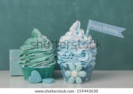 Happy Birthday cupcakes with flower, hearts and present - stock photo