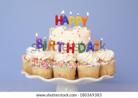 Happy Birthday lit candles cupcakes and cake on stand with blue background