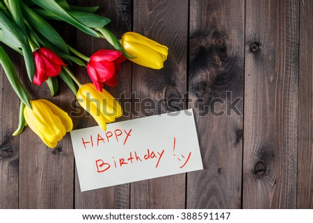 Happy birthday message with tulips on dark wooden table
