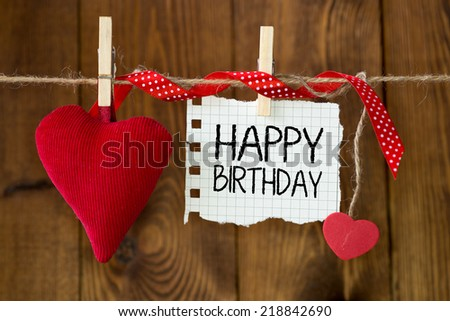 Happy birthday message written on a paper hanging on the clothesline on wooden background with two hearts - stock photo