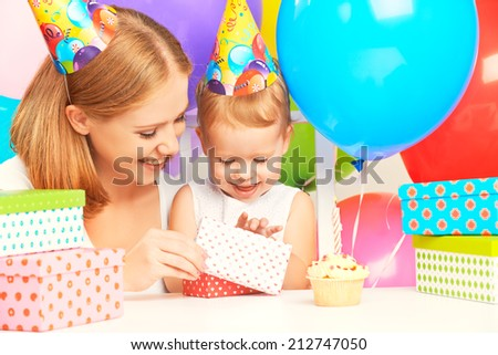 happy birthday. mother giving a gift to his little daughter with balloons and cake - stock photo