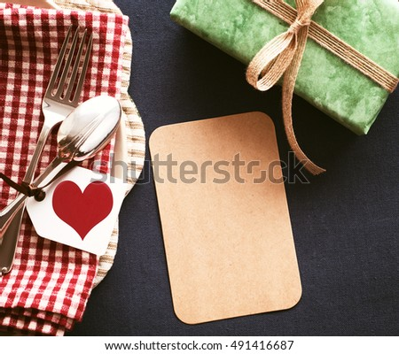 Happy Birthday or Valentine Day or Fathers Day Place setting and Blank Cards for your words, text or copy, a red heart tag and a green present in a casual still life style with Vintage sepia tint