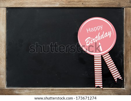 Happy Birthday rosette with festive striped ribbons on a vintage kids school slate with a wooden frame and blank black surface with copyspace for your text - stock photo