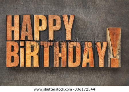 Happy Birthday! -  text in vintage letterpress wood type blocks stained by red ink  on a grunge metal background - stock photo