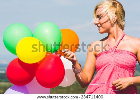 Happy birthday woman against the sky with rainbow-colored air balloons in hands