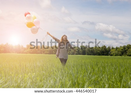 Happy birthday woman against the sky with rainbow-colored air balloons in hands. sunny and positive energy of nature. Young beautiful girl on the meadow in the park.