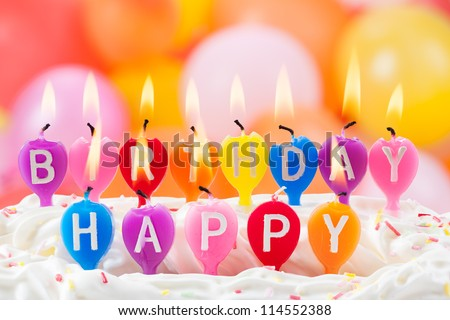 Happy birthday written in lit candles on colorful background - stock photo