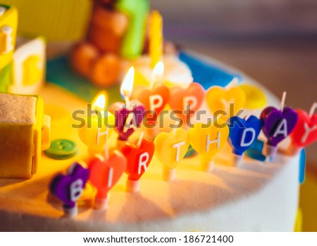 Happy birthday written in lit candles on colorful cake background - stock photo