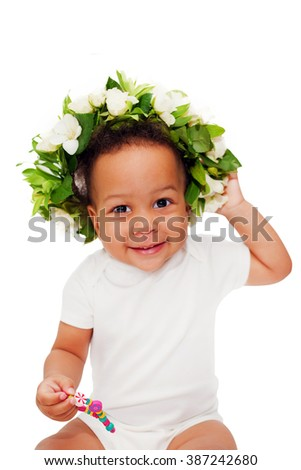 Happy black baby in a flower wreath. Isolated on white background