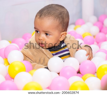 Happy black boy in colored ball on birthday on playground. The concept of childhood and holiday - stock photo