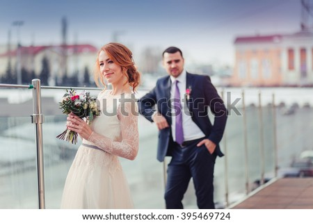 Happy black bride and groom softly hugging on the terrace with cityscape on background