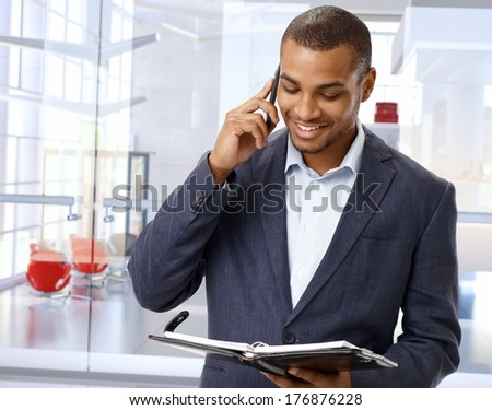 Happy black businessman on the phone in modern office lobby. - stock photo