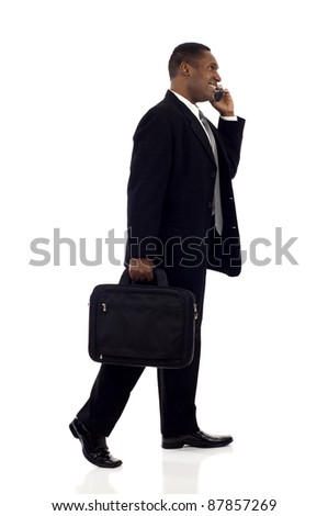 Happy black businessman talking on mobile phone while walking isolated white background - stock photo