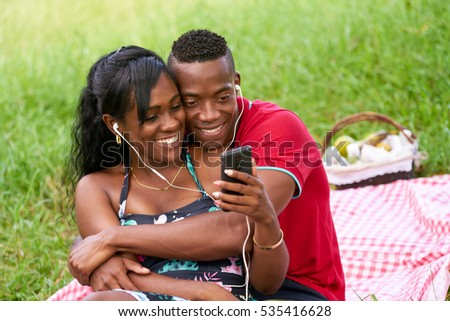 Happy black couple having fun in city park. Young african american man and woman listening to music and watching video on mobile phone.