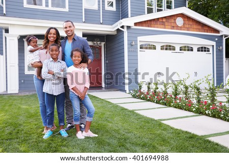 Happy black family standing outside their house - stock photo