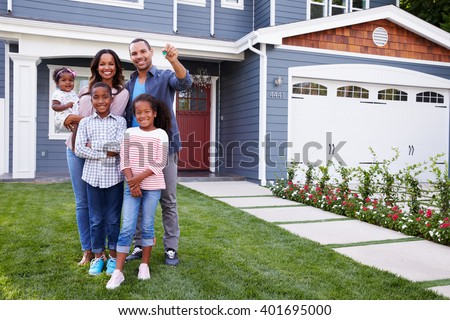Happy black family standing outside their house, dad holding the key - stock photo