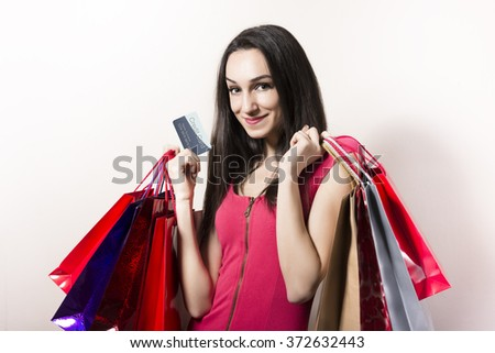 Happy black haired and pink dressed woman with shopping bags.