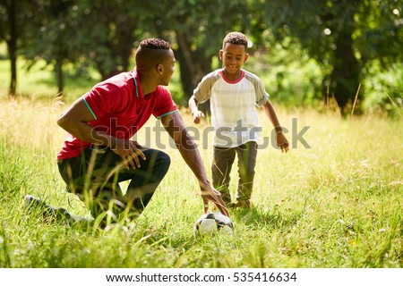 Happy black people doing sport practice in city park. African american family with father teaching son how to play football.