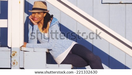 Happy black woman sitting on outdoor stairs laughing