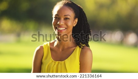 Happy black woman smiling in a park - stock photo