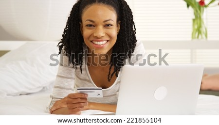 Happy black woman smiling with laptop and credit card - stock photo