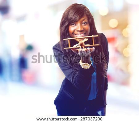 happy black woman with biplane - stock photo
