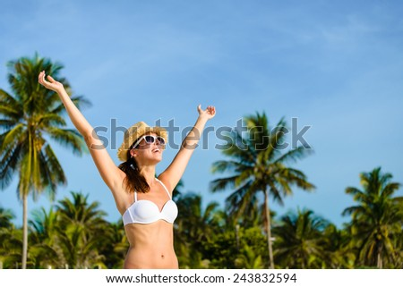 Happy blissful woman in white bikini enjoying tropical beach and caribbean summer vacation. Tanned brunette raising arms and enjoying freedom in Playa Paraiso, Riviera Maya, Mexico. - stock photo