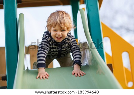 Happy blond boy having fun and sliding on outdoor playground. - stock photo