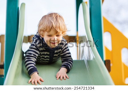 Happy blond boy having fun and sliding on outdoor playground. Active leisure with kids on spring day. - stock photo