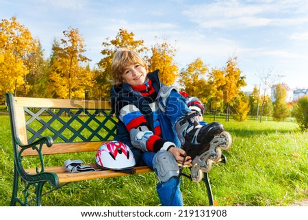 Happy blond boy putting on roller skates sitting on the bench in autumn park on sunny day - stock photo