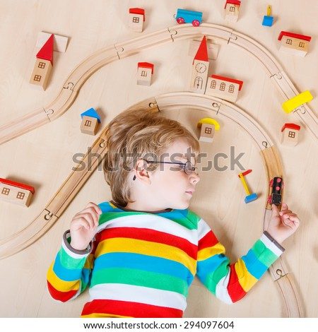 Happy blond child in glasses playing wooden trains and railroad indoor. Active kid boy wearing colorful shirt and having fun with building and creating. - stock photo