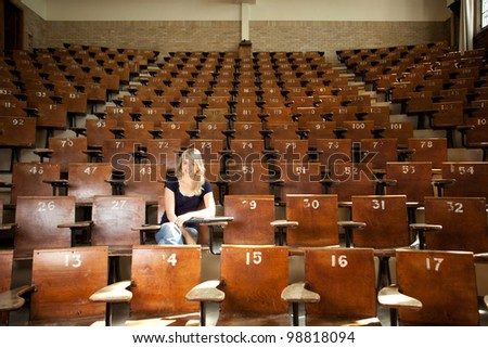 Happy blond college student alone in large lecture hall