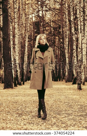 Happy blond fashion woman in classic coat walking in autumn forest  - stock photo