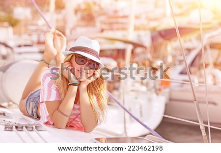Happy blond female lying down on sailboat and enjoying beautiful sunset, summer adventure on luxury water transport, pleasure and relaxation concept  - stock photo
