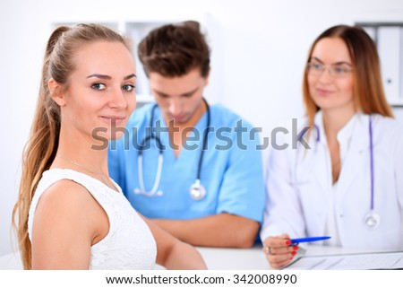 Happy blond female patient next to a few doctors in hospital sitting at the table