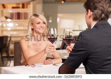Happy blond girl in love with nice man. Drinking wine in luxury restaurant