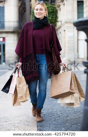 Happy blond girl looking satisfied after shopping and carrying few paper bags - stock photo