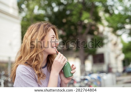 Happy Blond Girl Sitting at the Park, Drinking a Bottle of Cold Green Juice While Smiling Into the Distance. - stock photo