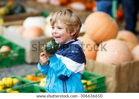 Happy blond kid boy holding green pumpkin on halloween or thanksgiving harvest festival or patch, outdoors - stock photo