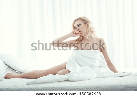Happy blond lady indoors sits in the bedroom - stock photo