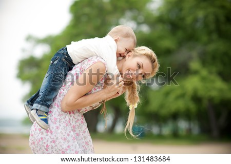 happy blond mom and one year old son enjoying nature together - stock photo