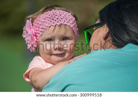 happy blond mom with her little son enjoying nature on a background of green leaves. Much of copyspace - stock photo