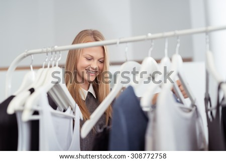 Happy Blond Woman behind Clothes Rail, Looking for Trendy Clothes Inside a Clothing Shop - stock photo