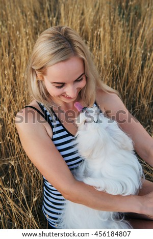 Happy blond woman hugging Maltese dog. Outside portrait.