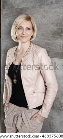 Happy blond woman leaning against grey wall, looking at camera.