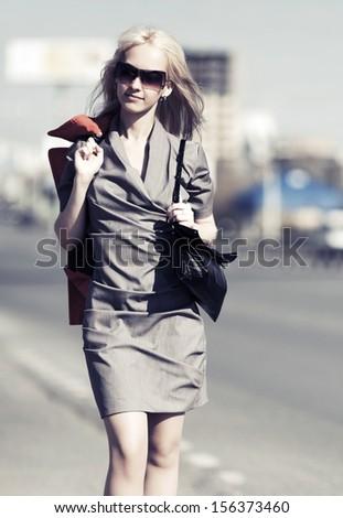 Happy blond woman walking on the city street - stock photo