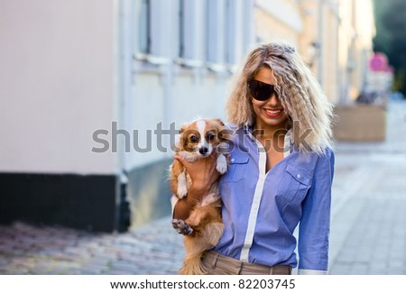 happy blond woman with chihuahua in downtown.