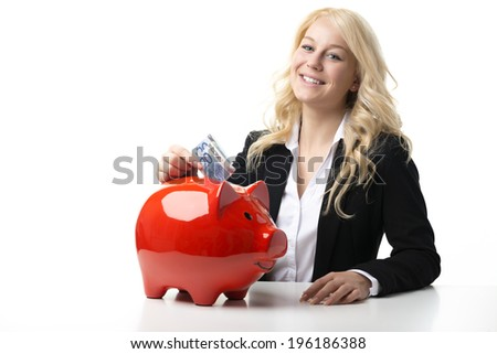 Happy blond women sitting at a table and throwing euro banknotes in a red piggy bank - stock photo