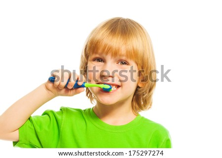 Happy blond 4 years old boy boy brushing teeth with toothpaste